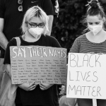 """Women at a Peaceful vigil for George Floyd at the Lincoln Memorial. They hold signs reading, """"SAY THEIR NAMES"""" and """"BLACK LIVES MATTER!"""""""