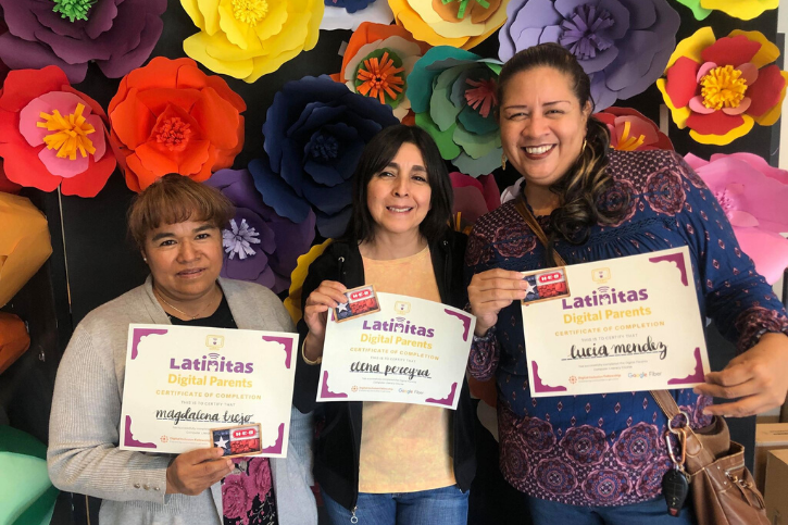 Three women stand in front of a wall decorated with colorful paper mâché flowers while holding up their program certificates.