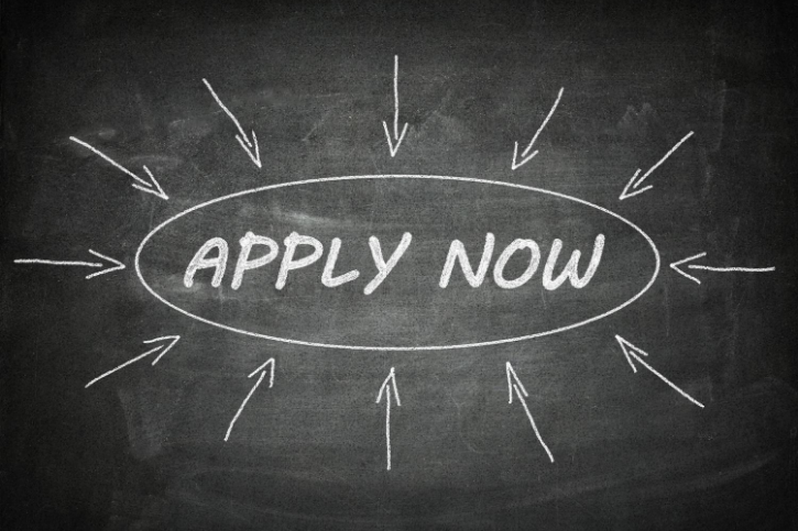 APPLY NOW written in a circle on a chalkboard. The circle is surrounded by arrows pointing to it.