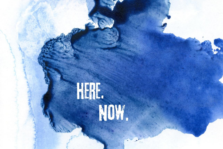 The words Here and Now in white on a splotch of blue set against a white background.