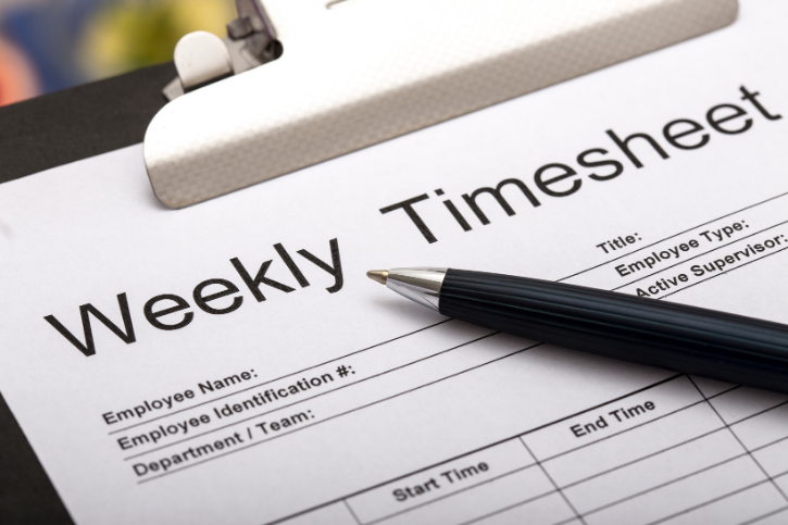 Close-up of a pen lying on a clipboard holding a weekly timesheet form