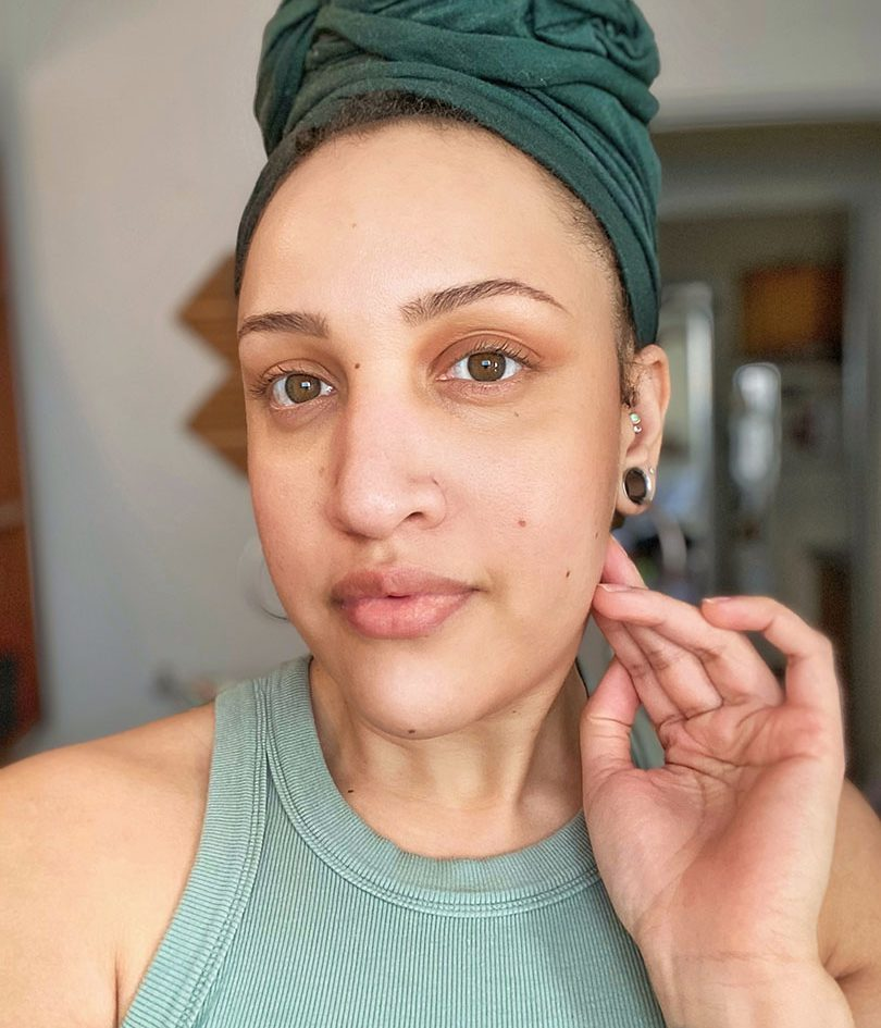 Pictured is Eva Davis. She is shown from the shoulders up, looking slightly to the left, with her right hand touching just below her ear. She has light brown skin. She is wearing a light green tank top, dark green head wrap, and silver hollow ear gages.