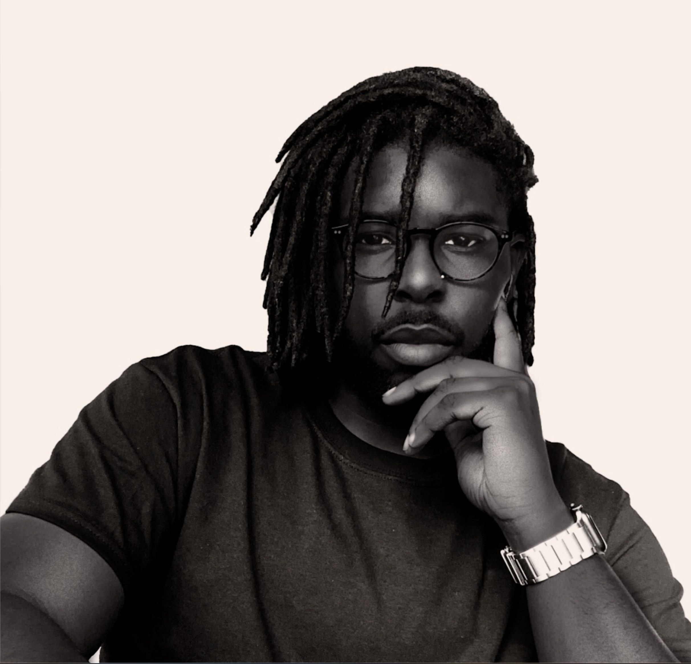 Pictured is Brandon Morayo sitting against a white background. He is shown from the chest up, leaning his right hand. He has dark skin and medium length dreadlocks. He is wearing a dark t-shirt, watch, and dark frame eyeglasses.
