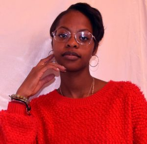 Pictured is Shakiyla Jamison from the shoulders up. She has dark brown skin and short dark pixie haircut. She is shown leaning slightly to the left with her left hand lightly touching her face. She is wearing wireframe eyeglasses, medium-sized gold hoop earrings, and a bright red-orange sweater.