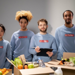Four people stand next to one another looking into the camera. They're wearing grey sweatshirts with the word VOLUNTEER in white type on a red background. In front of them is a table filled with boxes of vegetables and water bottles.