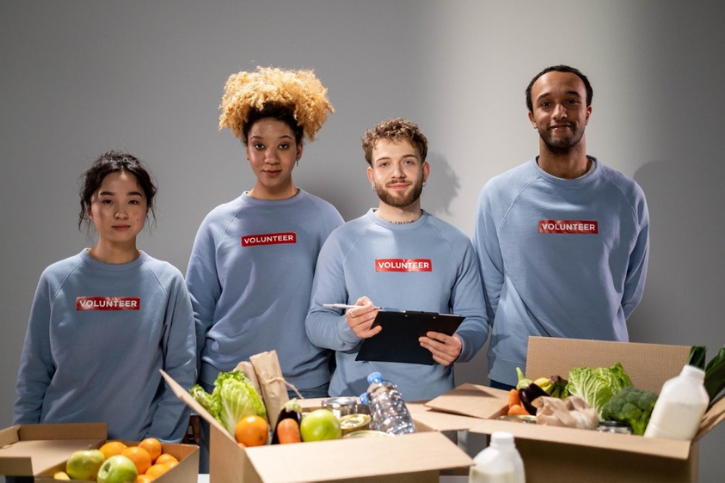 Four people stand next to one another looking into the camera. Theyre wearing grey sweatshirts with the word VOLUNTEER in white type on a red background. In front of them is a table filled with boxes of vegetables and water bottles.
