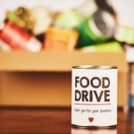"A can labeled ""Food Drive"" with a red heart. Behind it is a blurred box of canned goods."