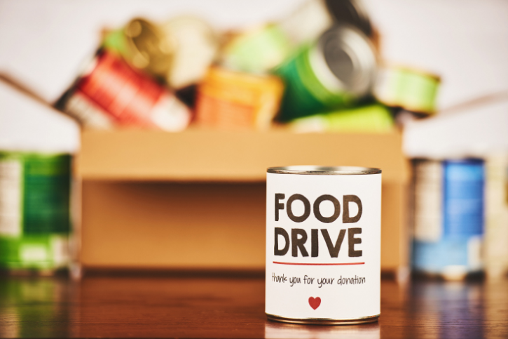 A can labeled Food Drive with a red heart. Behind it is a blurred box of canned goods.