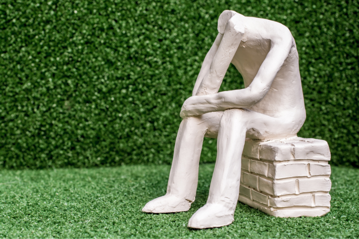 A toy-sized statue of headless person sitting on a brick wall. It sits in front of a fake green hedge.