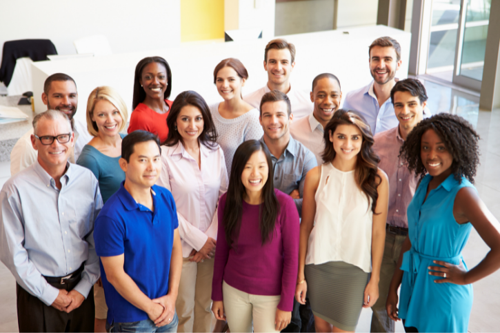 Fifteen people dressed in business casual stand in an office lobby and look up, smiling towards the camera.