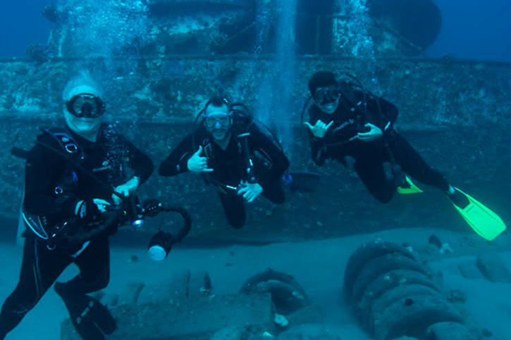 Three people in the ocean wearing scuba gear, smiling at the camera.